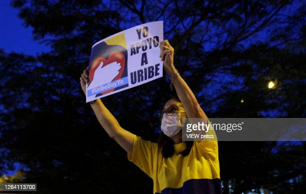 A supporter of former President and Senator Alvaro Uribe Velez wearing a protective mask shows a banner that reads in spanish I stand with Uribe...