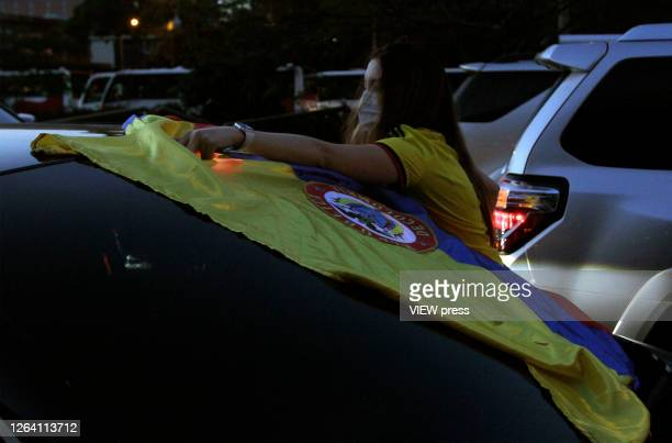 A supporter of former President and Senator Alvaro Uribe Velez wearing a protective mask places a colombian flag in a car during a protest against...