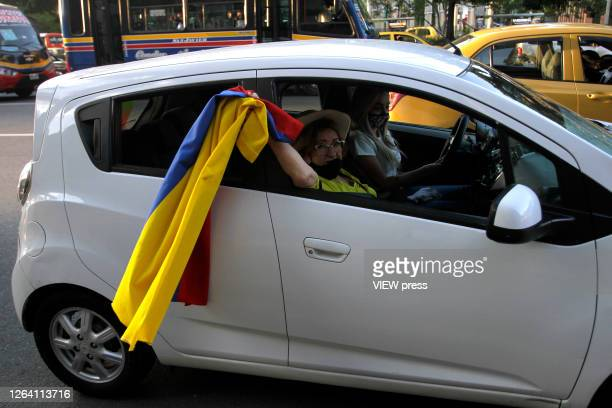 A supporter of former President and Senator Alvaro Uribe Velez wearing a protective mask waves a colombian flag during a protest against the Supreme...