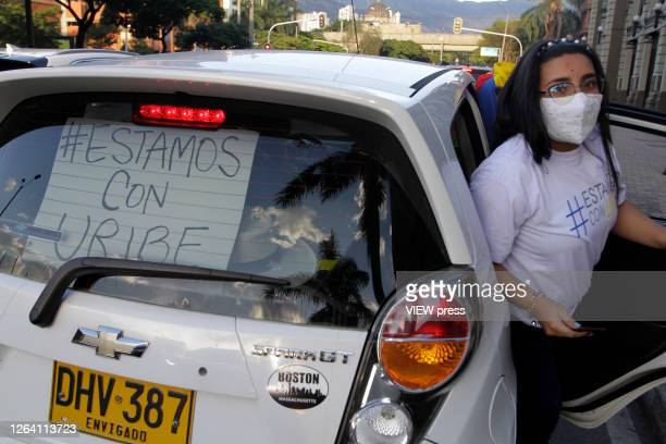 A supporter of former President and Senator Alvaro Uribe Velez wearing a protective mask gets off a car with a banner that reads in spanish we stand...