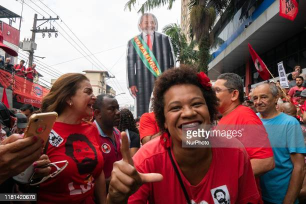 A supporter of former President Luiz Inacio Lula da Silva gestures a sign that means Free Lula in support of his freedom while awaiting his...