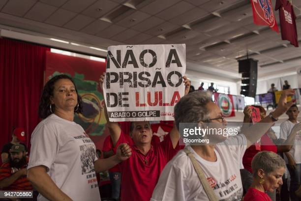 Supporter of former President Luiz Inacio Lula da Silva holds a sign during a protest against Lula's arrest warrant outside the metal workers' union...