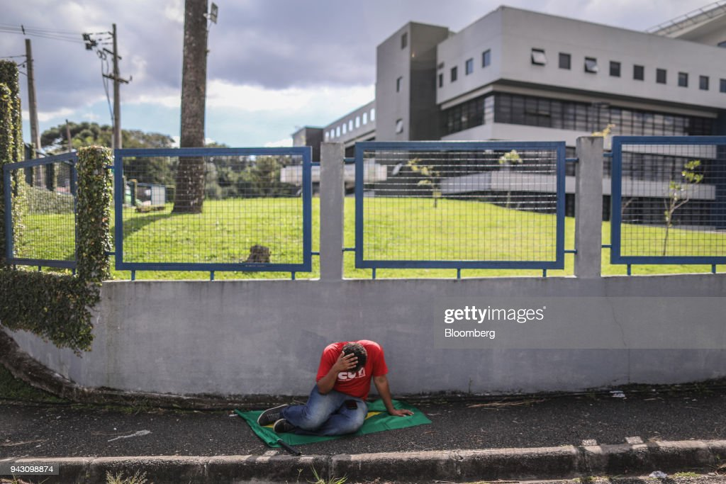 A supporter of former President Luiz Incio Lula da Silva sits outside of the Federal Police headquarters in Curitiba, Brazil, on Saturday, April 7, 2018. Lula said he will turn himself in to police, finally ending a tense stand-off with the authorities after he ignored a court-ordered deadline to begin a prison sentence. Photographer: Andre Coelho/Bloomberg via Getty Images