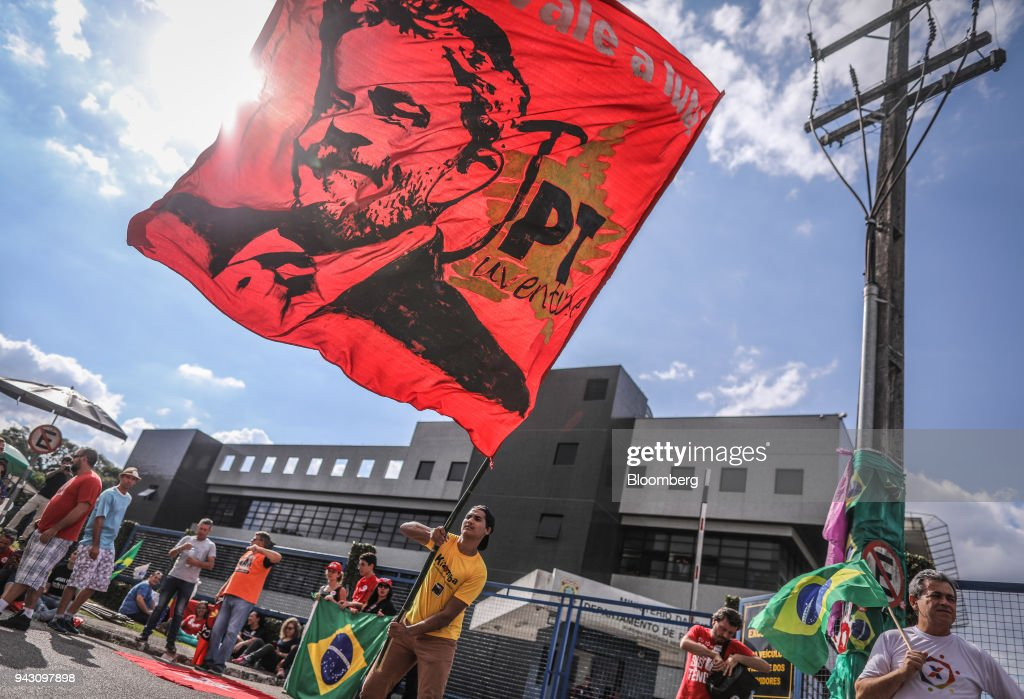 A supporter of former President Luiz Incio Lula da Silva waves a flag while waiting at the Federal Police headquarters in Curitiba, Brazil, on Saturday, April 7, 2018. Lula said he will turn himself in to police, finally ending a tense stand-off with the authorities after he ignored a court-ordered deadline to begin a prison sentence. Photographer: Andre Coelho/Bloomberg via Getty Images