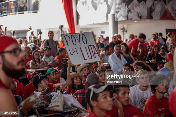 """Supporter of former PresidentLuiz Inacio Lula da Silva holds a sign that reads """"People in Struggle"""" while watching the Supreme Court's sentence..."""