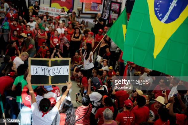 """Supporter of former PresidentLuiz Inacio Lula da Silva holds a sign that reads """"Democracy"""" while watching the Supreme Court's sentence ruling at the..."""