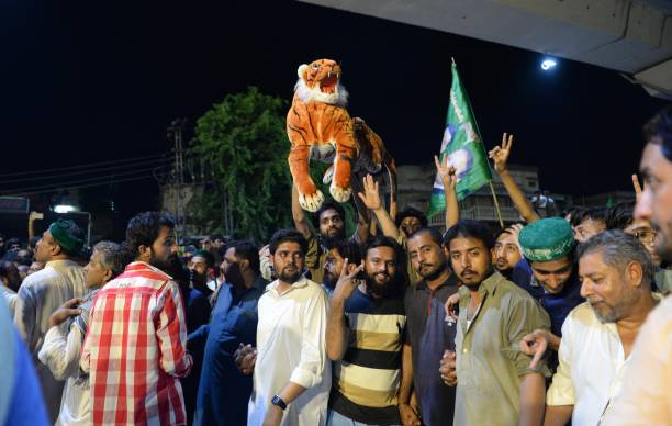 A supporter of former Prime Minister of Pakistan Nawaz Sharif holds a stuffed tiger an election symbol of the Sharif`s party as others chant slogans..