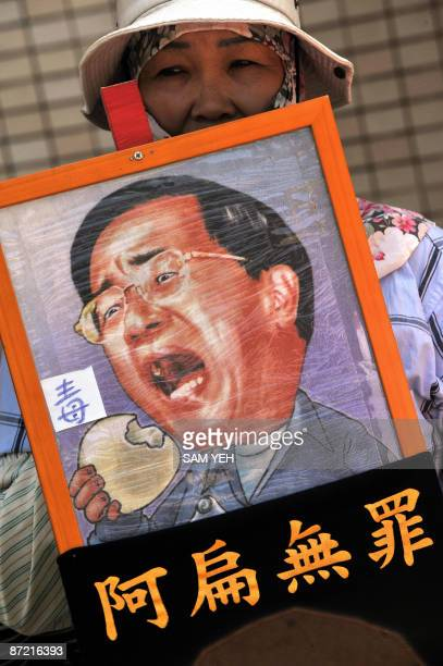 A supporter of former Taiwan president Chen Shuibian displays a Chen's placard outside the Tucheng Detention Centre in northern Taiwan on May 14 2009...