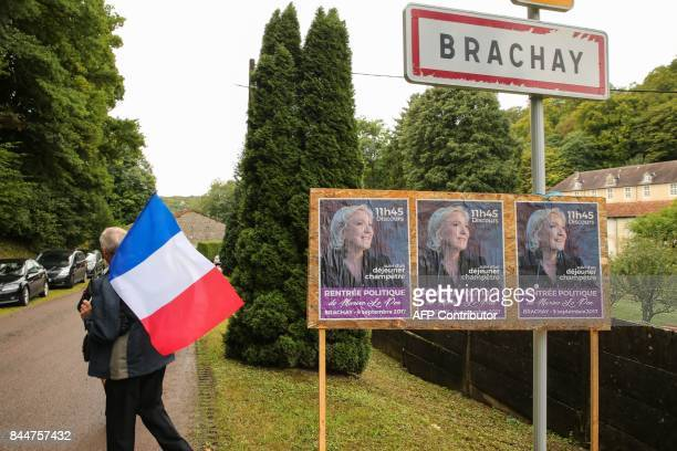 A supporter of France's National Front party holding the French flag walks past posters advertising a rally on September 9 2017 in Brachay...