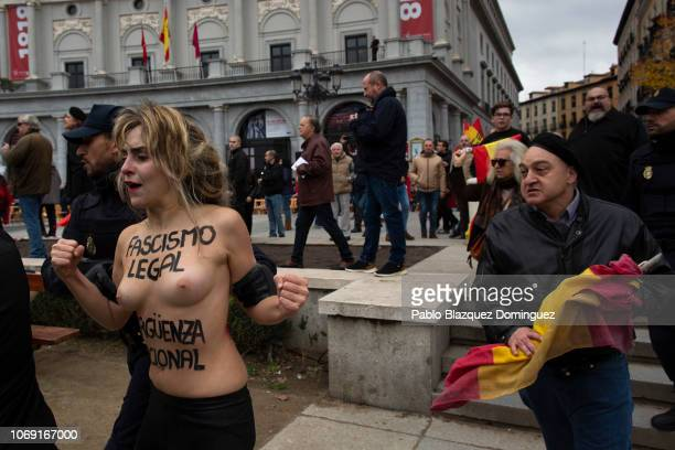 A supporter of Franco follows a FEMEN activist with body painting reading 'Fascism is legal National shame' as she protested during a rally...