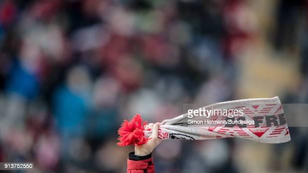 A supporter of Freiburg waves his scarf during the Bundesliga match between SportClub Freiburg and Bayer 04 Leverkusen at SchwarzwaldStadion on...