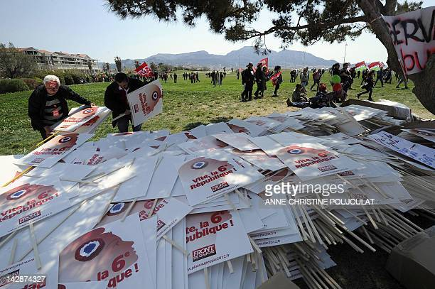 Supporter of French Front de Gauche leftist party's presidential candidate take placards upon their arrival to take part in a campaign meeting on...