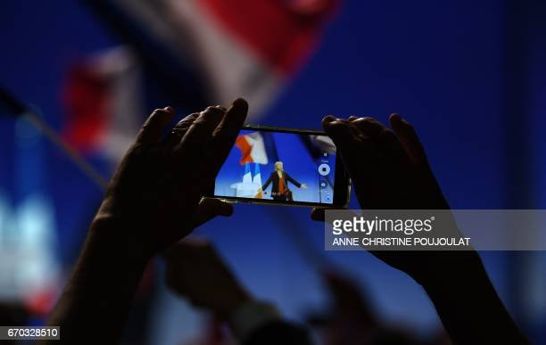 TOPSHOT A supporter of French presidential election candidate for the farright Front National party Marine Le Pen films with a mobile phone during a...