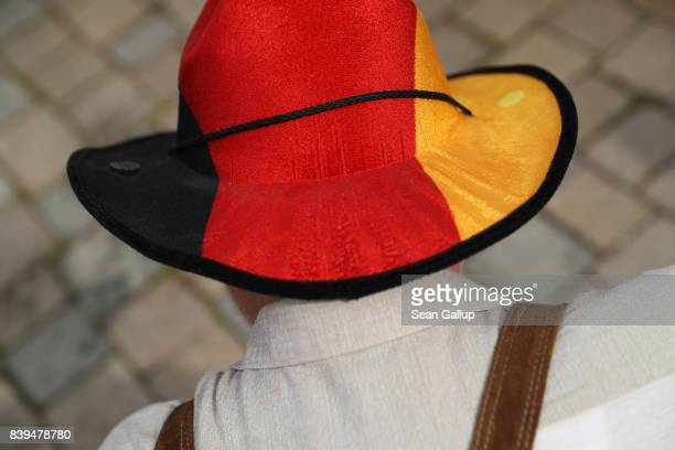 Supporter of German Chancellor and Christian Democrat Angela Merkel wears lederhosen and a cowboy hat in the colors of the German flag prior to...