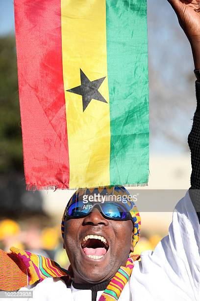 A supporter of Ghana holds a Ghanaian flag as he walks outside the Royal Bafokeng stadium as fans arrive for the Group D first round 2010 World Cup...