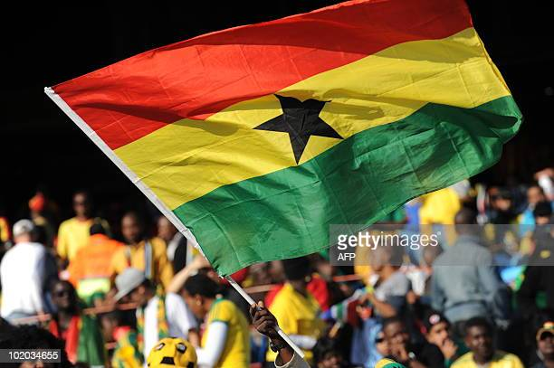 A supporter of Ghana holds a Ghanaian flag on June 13 2010 in Pretoria moments before the kickoff of the 2010 Football Wolrd Cup Serbia vs Ghana...