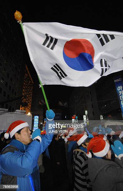 A supporter of Grand National Party presidential candidate Lee MyungBak waves the South Korean flag as he joins others to celebrate outside the...