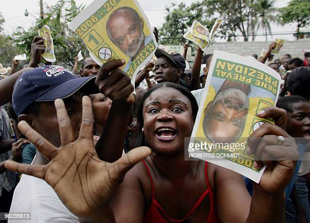 A supporter of Haitian presidential candidate Rene Preval shows a pamphlet with his image as she and thousands of others march in front of the...