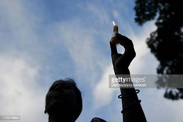 A supporter of Hindu yoga guru Baba Ramdev participates in a candle light rally following the recent gangrape and murder of a 20yearold college...