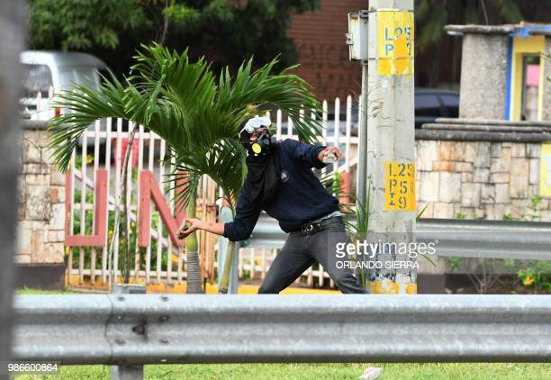 A supporter of Honduran opposition leader Manuel Zelaya a former president ousted by the military throws stones at riot police during a protest on...