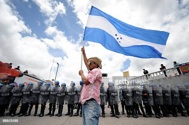 A supporter of Honduran President Manuel Zelaya holds a national flag in front of Honduran soldiers outside Toncontin international airport in...