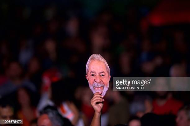 A supporter of imprisoned former Brazilian President Luiz Inacio Lula da Silva holds a mask depicting him during the 'Lula Livre' Music Festival in...