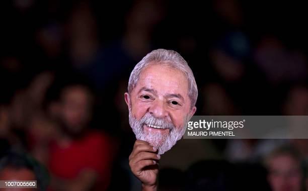 A supporter of imprisoned former Brazilian President Luiz Inacio Lula da Silva holds a mask depicting him during the Lula Livre Music Festival in Rio...