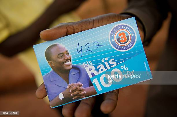 A supporter of incumbent president Joseph Kabila shows a card of the candidate marked also with the number of this supporter's candidate for the...