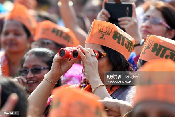 A supporter of Indian Prime Minister and Bharatiya Janata Party Leader Narendra Modi uses binoculars to view the scene at a state assembly election...