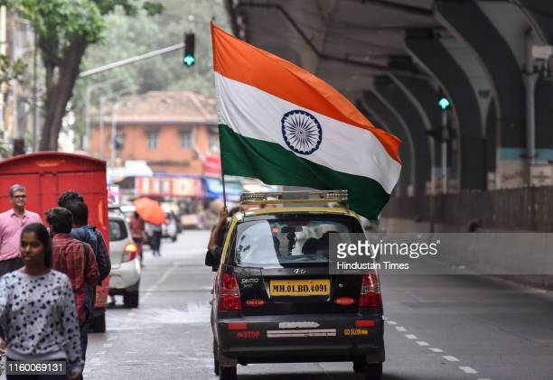 A supporter of Indian Prime Minister Narendra Modi holds a Indian flag as he travels by taxi to celebrate the government revoking Kashmir's special...