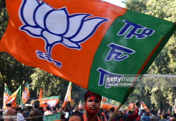 A supporter of India's ruling Bharatiya Janata Party holds a flag as he celebrates outside the party headquarters in New Delhi on December 18 with...