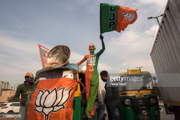 A supporter of India's ruling party Bharatiya Janata Party India's ruling political party painted with party flag shout slogans during electioneering...