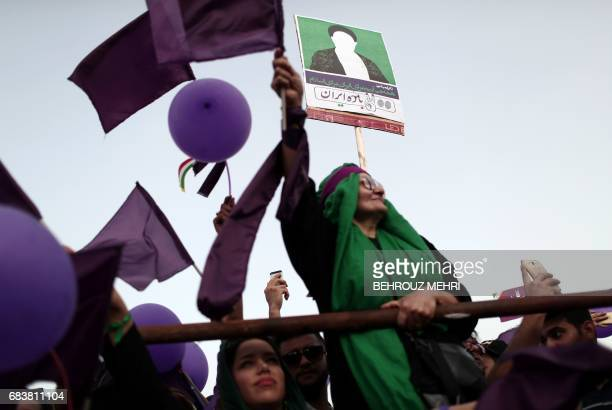 A supporter of Iranian President and candidate in the upcoming presidential elections Hassan Rouhani holds a banner bearing an image representing...