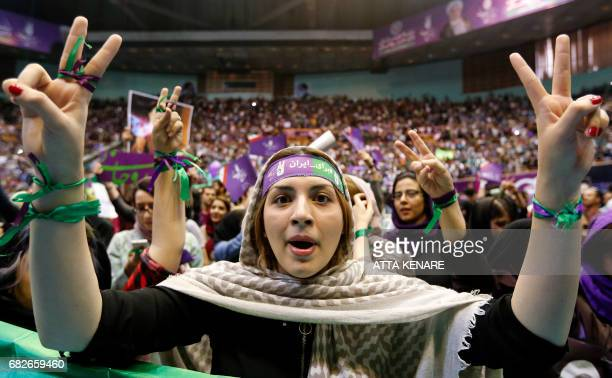 A supporter of Iranian President and presidential candidate Hassan Rouhani raises the victory gesture with both hands at a campaign rally in the...