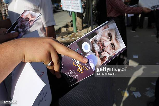 A supporter of Iranian presidential candidate and lead nuclear negotiator Saeed Jalili hands out leaflets with his image during a campaign rally...