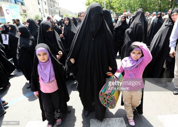A supporter of Iranian religious hardliners with two children takes part in a demonstration after the weekly Friday prayer in Tehran on May 16 2014...