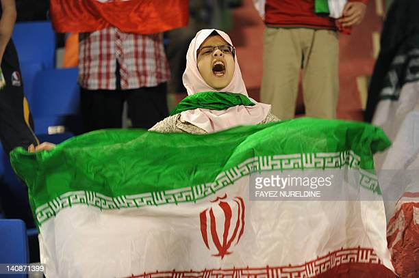 A supporter of Iran's Piroozi Athletic club celebrates with a national flag after her team scored a goal against Saudi Arabia's AlHilal during their...