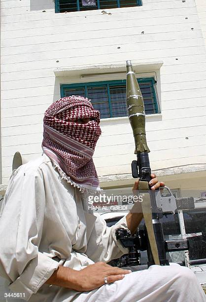 A supporter of Iraqi Shiite cleric Moqtada alSadr guards the bullet riddled office of his movement in the Iraqi city of Amara 19 April 2004 Clashes...