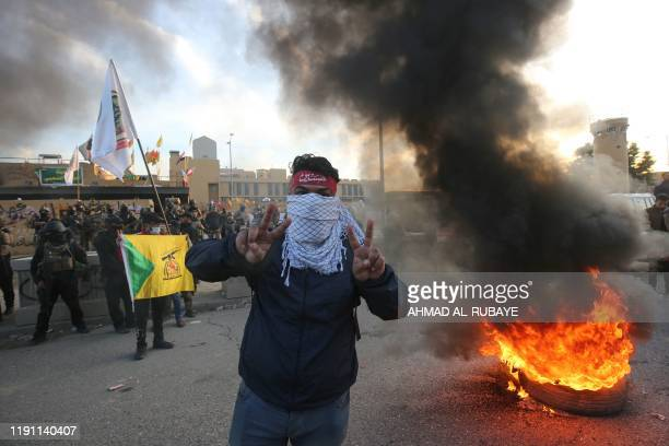 TOPSHOT A supporter of Iraq's Hashed alShaabi paramilitary force flashes victory signs during a protest outside the US embassy in the Iraqi capital...