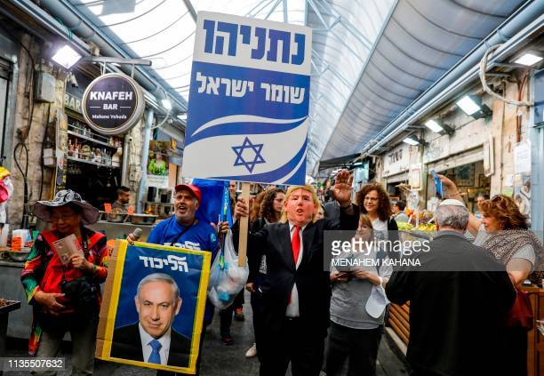 Supporter of Israeli Prime Minister Benjamin Netanyahu wearing a mask with the face of US President Donald Trump marches with a sign reading in...