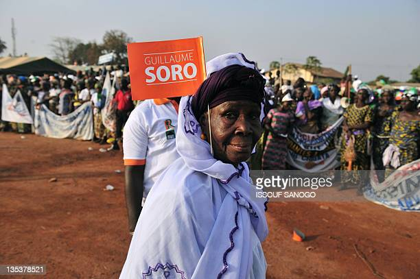 Supporter of Ivory Coast Prime Minister and leader of news forces the former rebel groupe looks on during a legislative election meeting in...