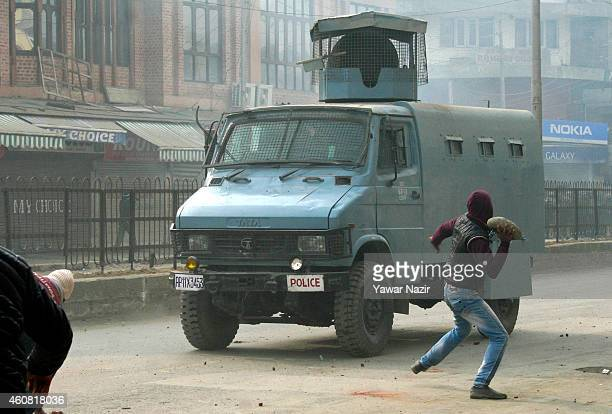 A supporter of Jammu and Kashmir Liberation Front throws stones towards an Indian paramilitary vehicle during a demonstration on December 24 2014 in...