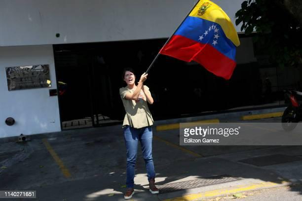 A supporter of Juan Guaidó waves a Venezuelan flag on April 30 2019 in Caracas Venezuela Through a live broadcast via social media Venezuelan...