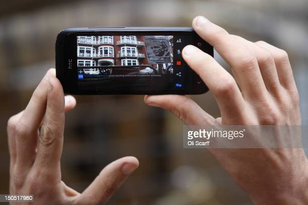A supporter of Julian Assange the founder of the WikiLeaks whistleblowing website uses his mobile phone to video the Ecuadorian Embassy where Mr...