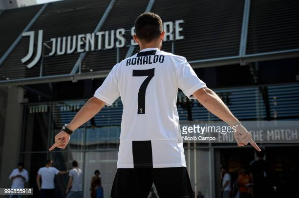 Supporter of Juventus FC poses with Cristiano Ronaldo's Juventus official jersey in front of Juventus Store. Juventus FC and Real Madrid CF announced...