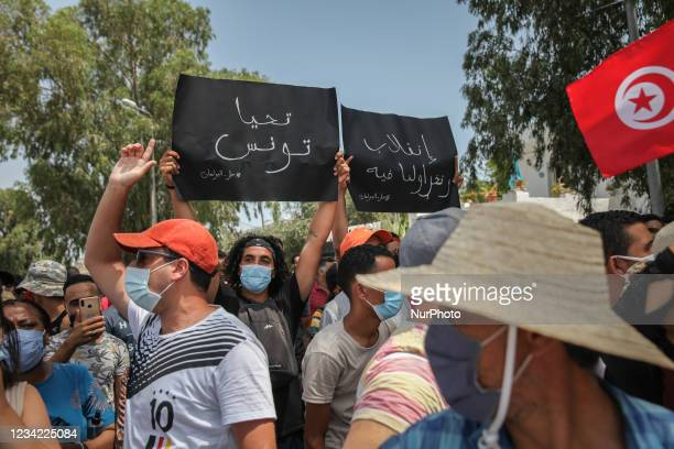 Supporter of Kais Saied raises a placard that reads in Arabic, long live Tunisia, dissolve the parliament, as another raises another placard that...