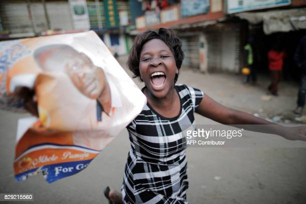 Supporter of Kenyan opposition presidential candidate Raila Odinga takes part in a march in the Mathare slum in Nairobi on August 10 following an...