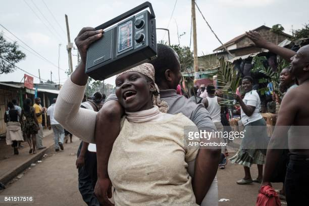 A supporter of Kenya's opposition National Super Alliance celebrates as she listens to a radio on a motor bike in a street of Kibera slum in Nairobi...
