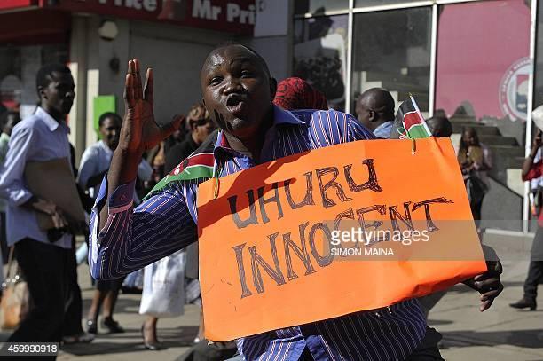A supporter of Kenya's President Uhuru Kenyatta celebrates in the streets of Nairobi following the International Criminal Court's ruling to drop...