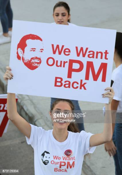 A supporter of Lebanon's resigned prime minister Saad Hariri holds up a placard demanding his return from Saudi Arabia on the starting line of...